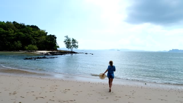 Drone shot o a young woman running on the beach in Thailand video