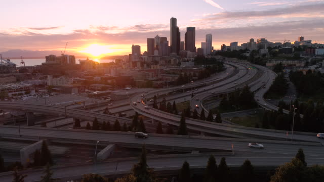 Drone Shot of Seattle with Epic Glowing Sunset on Freeway and Downtown Skyscraper Buildings in City Skyline video