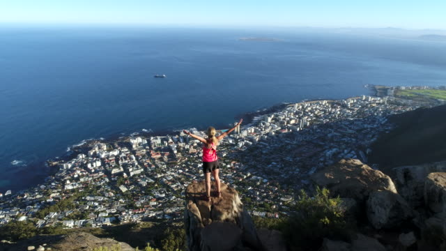 Drone shot of woman reaching mountain top video