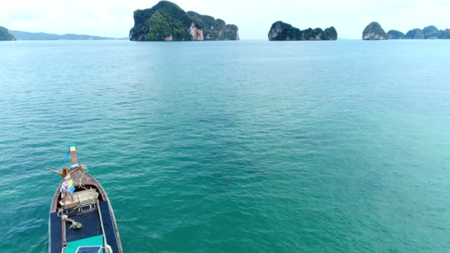 Drone shot of woman standing on a longtail boat in tropical settings video
