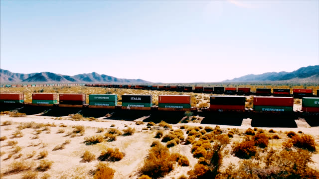 Drone shot revealing a moving container train barreling down a railroad in the middle of the American desert. video