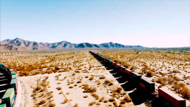 Drone shot tracking left to right over a container freight train as it barrels down a railroad in the arid American desert. video