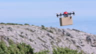 SLO MO TS Drone transporting package above the hilltops video