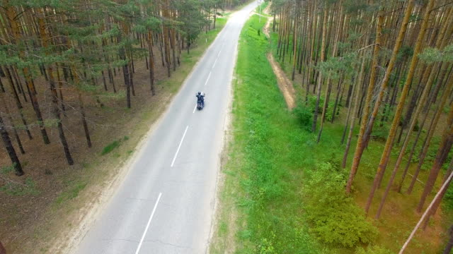 Drone video of a motorcyclist driving away. video
