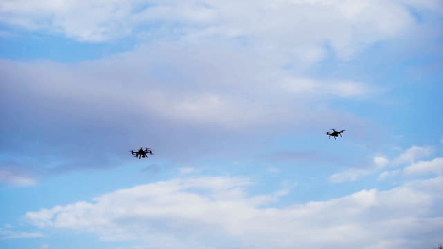 Drones hovered in the background of the sky. Modern technology in operation video