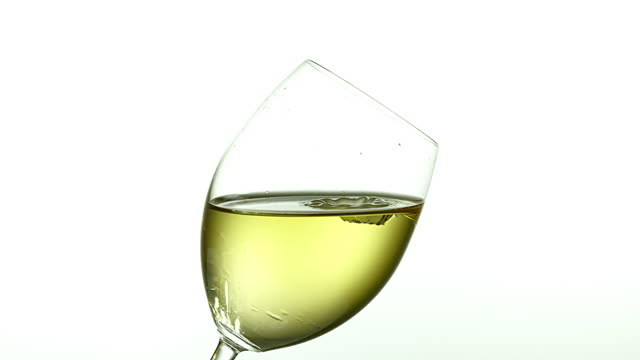 Drop of White Wine falling into Glass, against White Background, Slow motion 4K video