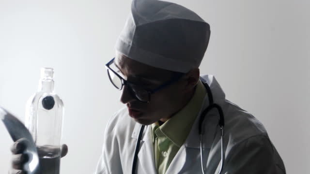 Drunk doctor makes a diagnosis. A medical worker drinks vodka. video
