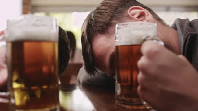 Drunk friends sleeping in a bar video
