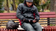 Drunk man holding empty bottle of beer, spitting, poor manners, degradation video