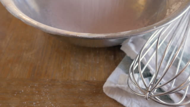 Dry Cake Ingredients Are Sifted into a Metal Mixing Bowl on a Wooden Table - 4K video