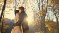SLO MO Dry leaves falling over loving couple in embrace video