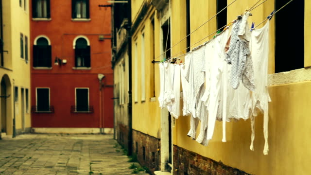 Drying laundry waving at the old italian street, Venice. video