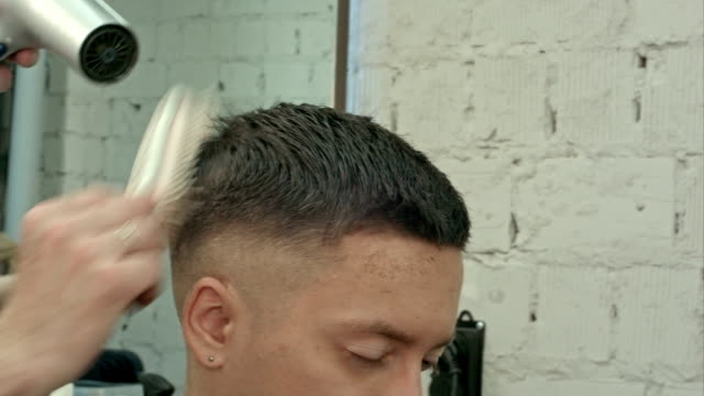 drying, styling men's hair in a beauty salon video