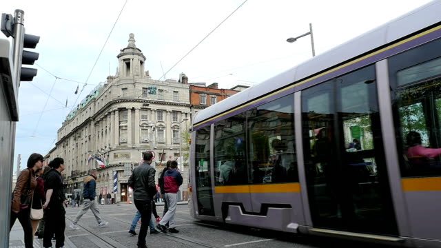 Dublin city center with luas crossing and pedestrians video
