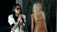 Duet African American man and a blonde woman singing. Slow motion video