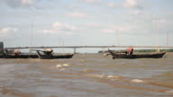 dugout canoes moored on the bank of the river on a windy day video