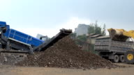 Dump truck being loaded with rock by shovel. Excavator operating in a rock quarry video