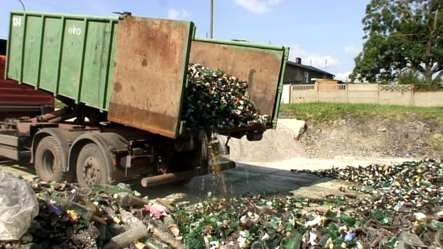 Dump truck reloading bottles in glass recovery plant video
