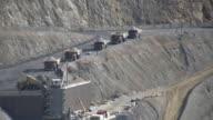 dump trucks dumping rock into in pit crusher video