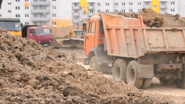 Dump trucks working on a construction site video