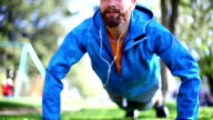 Early 30's bearded man exercising in park. video