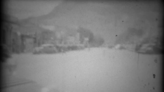 1937: Early car tourism driving through the center of town 1st person pov. video