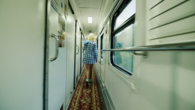 Early morning on the road. Menshina goes along the corridor of the passenger car. Steadicam shot video