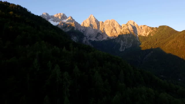 AERIAL: Early morning sun shining on big rocky mountains, European Alps video
