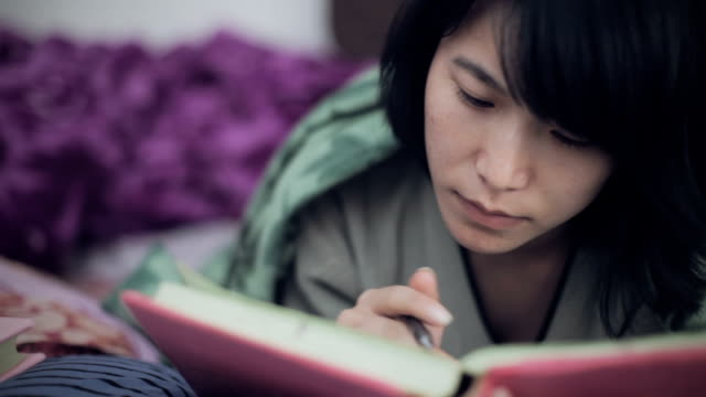 East Asian college girl studying in bed. video