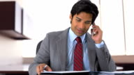 East Indian businessman shuffling through notes and talking on phone video