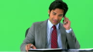 East Indian businessman shuffling through notes and talking on greenscreen video