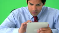 East Indian businessman working on tablet on greenscreen video