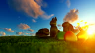 Easter Eggs and Chocolate Bunnies on green meadow against beautiful sunrise video