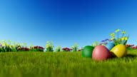 Easter eggs on green meadow over blue sky video