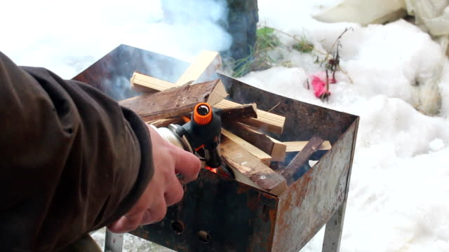 Eastern Europe: Lifestyle. Man ignites fire wood in grill with a gas torch. video
