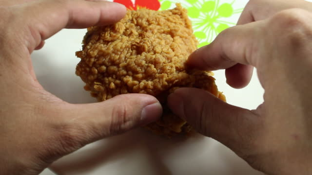 Eating fried chicken strip on the dish video