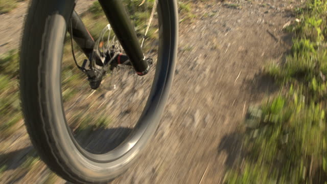 CLOSE UP: E-bike wheel and big mountainbike tire spinning fast on gravel path video