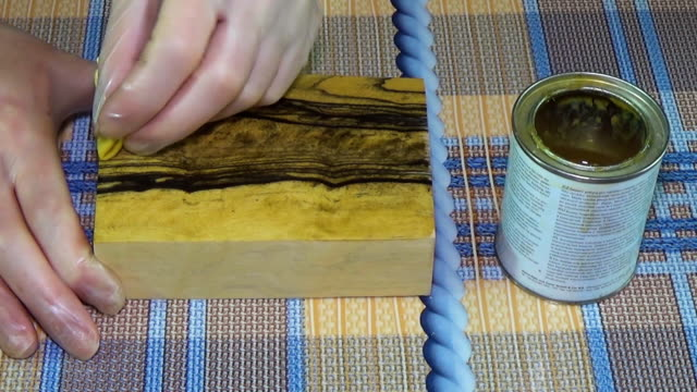 Ebony wood. The bar of solid wood is covered with stain. The girl covers a bar of rare wood with lacquer. The joinery impregnates the wood with wax. Checkered background. Continuation of coating, second layer video