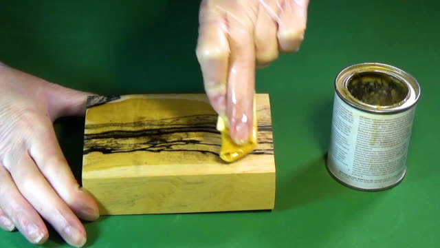 Ebony wood. The bar of solid wood is covered with stain. The girl covers a bar of rare wood with lacquer. The joinery impregnates the wood with wax. Chroma Key video