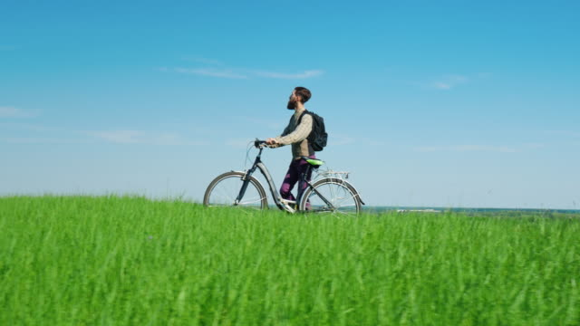 Ecotourism - a man drives a bicycle through a green meadow against a bright blue sky. An idyllic landscape, an environmentally friendly place video