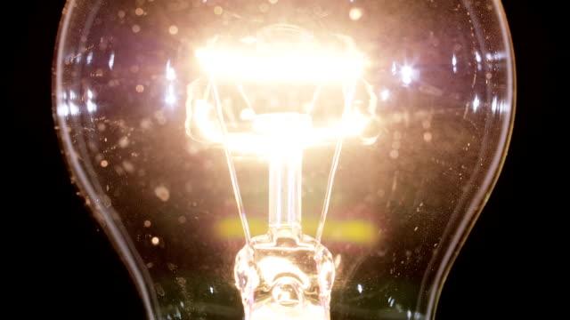 Edison lamp light bulb blinking over black, macro view video, looped video