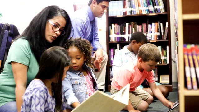 Education. brarian reads book to elementary students in library or classroom. video