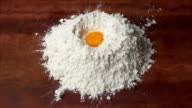 Egg falling on flour in slow motion video