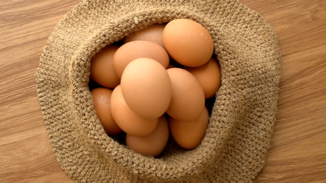 Eggs on sack back with wooden table backgroud.  Top view and panning. video