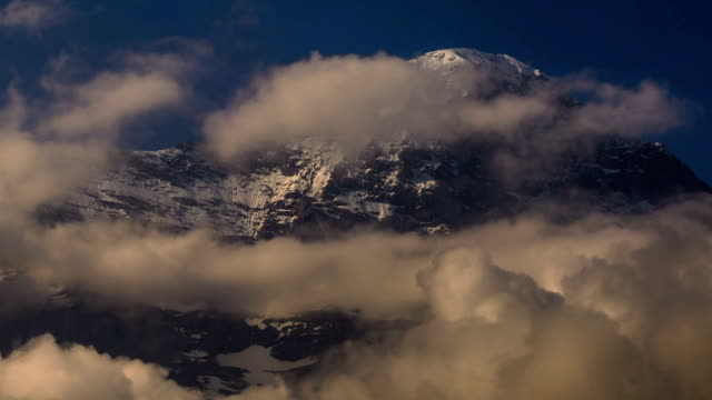 Eiger North face covered in snow and ice churning clouds video