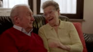 Elder couple cuddling on the couch video