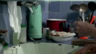 Elder woman working in average Cuban kitchen video