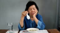 Elderly asian woman bored with food video