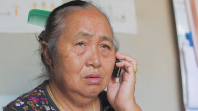 Elderly asian woman talking on mobile phone. video