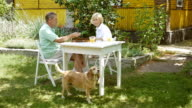 Elderly couple playing a board game in the garden. video